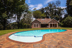 Pool Home Lifestyle. Clear blue pool located in front of small stone cottage home in surrounding vegetation Stock Image