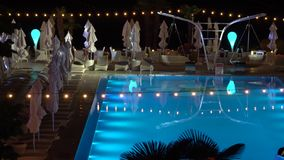 Pool illuminated . In the foreground are seen palm trees. Pool illuminated at night. In the foreground are seen palm trees stock video footage
