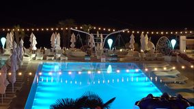Pool illuminated at night. Near the pool can be seen in the chair Woman stock footage