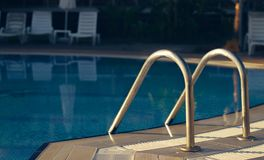 Pool inox handrails view on morning dawn lights. Clear water Royalty Free Stock Images