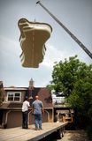 Pool installation. Two crain professionals guiding a fiberglass pool over a two story home Stock Photos