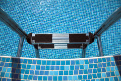 Pool ladder down, blue tiles Royalty Free Stock Photography