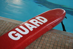 Pool life-saving float. A red life-saving flotation device with the word 'Guard' across it, on the edge of a swimming pool Royalty Free Stock Photo