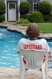 Pool lifeguard. Young man sitting by a private pool with a lifeguard shirt on royalty free stock image