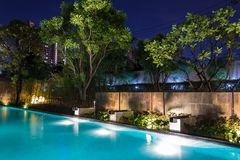 Pool lighting in backyard at night for family lifestyle and living area. Luxury design with good light and clean landscaping. stock images