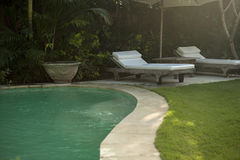 Pool with Loungers. Hotel garden and swimming pool in an exotic location stock photo