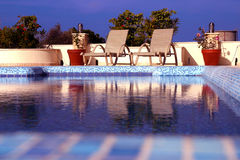 Pool and Loungers. Sun loungers sitting invitingly next to a swimming pool Stock Images