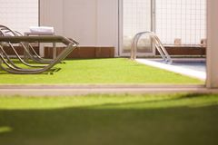 Pool loungers without people. Part of pool in a hotel with sunbeds without people royalty free stock photos