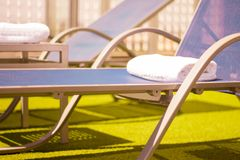 Pool loungers without people. Part of pool in a hotel with sunbeds without people royalty free stock photo