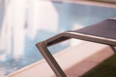 Pool loungers without people. Part of pool in a hotel with sunbeds without people royalty free stock images