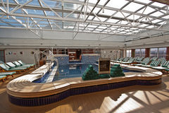Pool on luxury cruise liner. Cool inviting pool on the top deck of a luxury cruise liner surrounded by empty recliner chairs for relaxation under a glassed in royalty free stock images