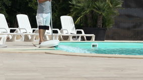 Pool Maintenance Works. An employee doing maintenance work of a swimming pool at a summer resort stock video