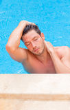 Pool man. Cheerful good-looking wet hair man in the blue pool relaxing royalty free stock images