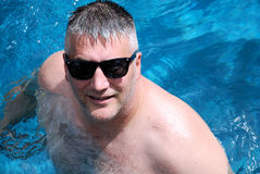 Pool Man. A attractive man relaxing and cooling off in the waters of an inviting tropical pool Stock Photos