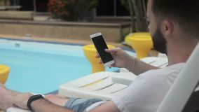 At the pool man holds a phone with the Internet at a luxury hotel. stock footage