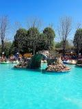 Pool met blauw water en watermachines als aantrekkelijkheden in het stadspretpark stock afbeelding