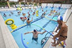 Pool met kinderen en ouders in water het spelen De pret van de familie Stock Afbeelding