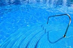 Pool mit Treppeschiene des blauen Wassers am Tageslicht Lizenzfreies Stockfoto