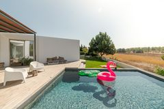 Modern house with garden swimming pool and wooden deck. Pool Modern house with garden swimming pool and wooden deck royalty free stock images