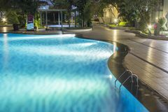 Pool at night with lush greenery and lighting for home design and landscaping in the backyard. Night shadows and reflections on t. He pool water. Ladder royalty free stock photo