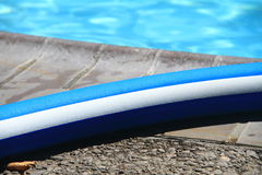 Pool noodle by the swimming pool Royalty Free Stock Images