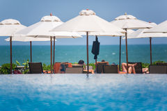 Pool and Ocean with beach chairs and umbrellas Royalty Free Stock Photography