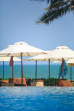 Pool and Ocean with beach chairs and umbrellas Royalty Free Stock Image