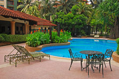 Free Pool Of A Condominium With Deckchair And Table Chair Royalty Free Stock Image - 34884636