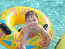 Pool Party. A young boy is all smiles from the enjoyment of swimming in a pool Royalty Free Stock Photos