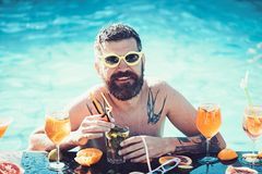 Pool party, vitamin and dieting. Cocktail with fruit at bearded man in pool. Man swimming and drink alcohol. Relax at royalty free stock image