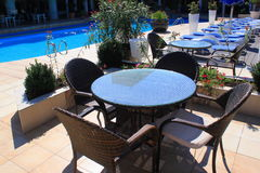 Pool patio rattan furniture. Patio furniture by the pool and sunbeds. A patio set along side of a pool Stock Images