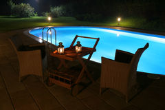 Pool and Patio by Night. Beautiful outdoor pool and patio make for a very romantic setting in this private backyard stock photography