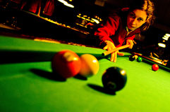 Pool player. A female pool player bending over the green table and ready to hit the white ball Royalty Free Stock Photos