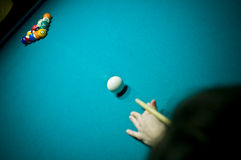 Pool player. A female pool player bending over the green table and ready to hit the white ball Stock Photo