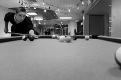Pool Player Shooting. A young man shooting pool with motion blur on the pool balls. Shallow depth of field royalty free stock image