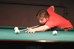 A pool player takes aim at the ball. Billiards player plays Billiards aiming at the ball stock images