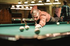 A pool player takes aim at the ball. Billiards player plays Billiards aiming at the ball royalty free stock images