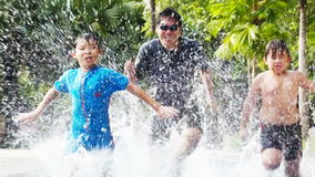 Pool racing. Two Asian boys racing with their father in a pool stock footage