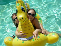 ON a pool raft. A picture of a teen gril and her sister wearing sunglasses in the pool on a dragon pool raft Stock Photos