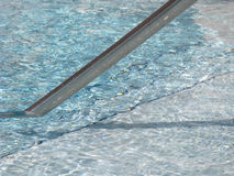 Pool Rail. The railing and rippled water of a swimming pool Stock Photo
