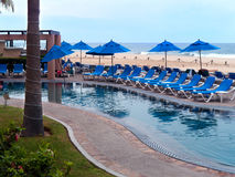 Pool with recliners blue umbrellas and beach. At San Jose del Cabo Baja Mexico. Sea of Cortez has a very nice and warm water good for vacationing Royalty Free Stock Photos