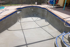 Pool resurfacing and gray cement bond coat. Empty pool repair work new gray cement bond coat being applied in preparation for new Diamond Brite pool plaster Stock Image