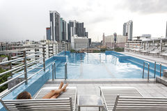 Pool on a roof. Girl relaxing in the pool on the roof of resort with urban view on skyscraper in Bangkok city Royalty Free Stock Image