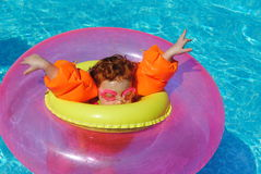 Pool Safety. A young girl swimming in a shimmering blue pool wearing a life preserver also bright orange arm swimming safety floaters inside a smaller bright royalty free stock images