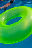 Pool scenes. Bright colored floater in a swimming pool with someone swimming Stock Images