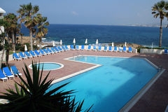 Pool by the sea. Surrounded by palms Stock Photography