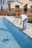 Pool Service. Service man cleaning pool filters, removing leaves that have fallen in pool this fall Stock Images