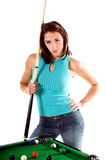 Pool Shark. Sexy young woman in jeans and a hat with a pool cue and standing at  the table Royalty Free Stock Image