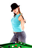 Pool Shark. Sexy young woman in jeans and a hat with a pool cue and standing at the table Royalty Free Stock Photography