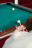 Pool shot. Pool player lining up a shot on the nine ball, with selective focus on hand, cue and cue ball Stock Image